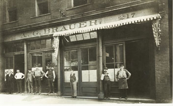 The Brauer staff is here shown in 1884 in front of the Company's second location. A.G. Brauer is the third man from the right.